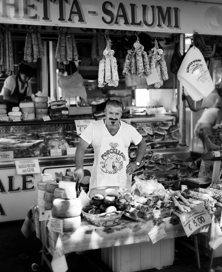 A butcher standing in front of his booth